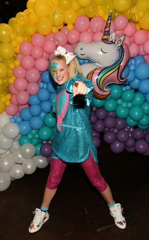 JoJo Siwa playfully dances by over-the-top rainbow decor.