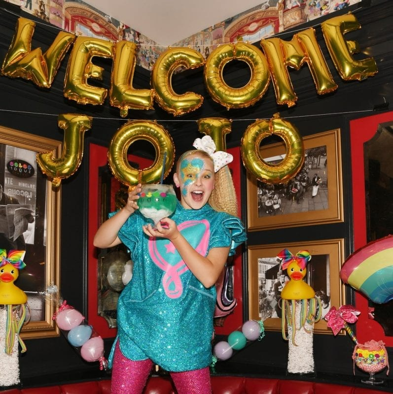 JoJo Siwa poses with non-alcoholic ocean blue goblet and JoJo themed decorations.