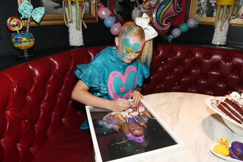 JoJo Siwa signs picture of herself to hang on Sugar Factory wall.